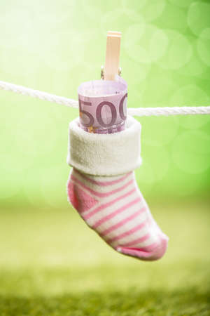 billets euros: Baby Sock With Dollar Hanging On Rope Using Wooden Clip