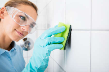 Young Woman With Protective Eyewear Cleaning The White Tile Of The Wall Using Sponge