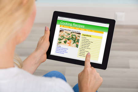 tab: Close-up Of Woman Hand Using Digital Tablet For Learning Recipe On Website