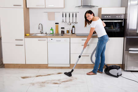 Young Happy Woman Cleaning The Floor Of The Kitchen Using Vacuum ...