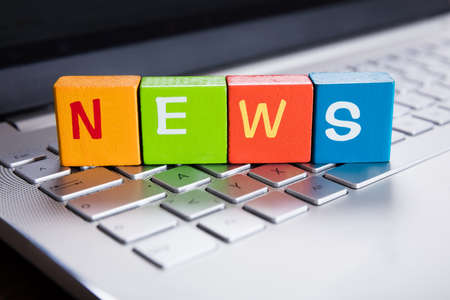 News Text On Colorful Cubes Over Laptop Keyboard Stock Photo