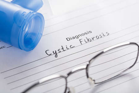cystic fibrosis: Close-up Of Inhaler Mask And Glasses On Paper With Text Diagnosis Cystic Fibrosis