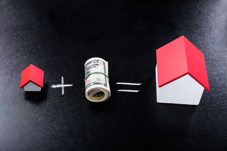 Close-up Of Rolled Dollar Banknotes And House Models On Blackboard