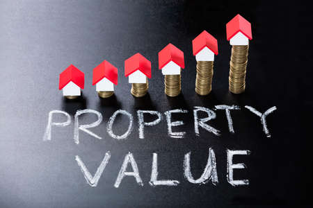 House Models On Stacked Coins Showing Property Value Concept On Blackboard
