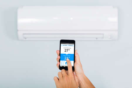 Woman Hand Setting Temperature Of Air Conditioner Using Smartphone App At Home Stock Photo