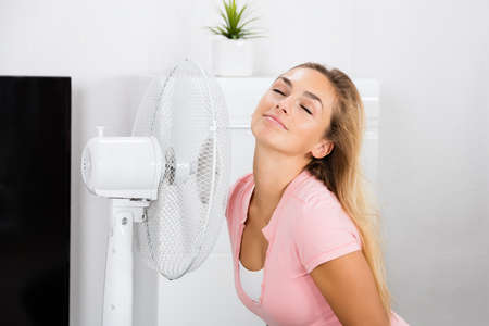 Young Smiling Woman Sitting On Couch In Front Of Fan During Hot Weather At Home