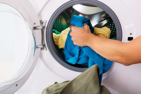 put: Close-up Of Woman Hand Loading Dirty Clothes In Washing Machine Stock Photo