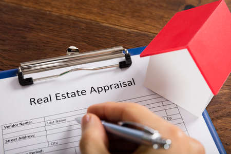 Close-up Of Person Hand Filling Real Estate Appraisal Form With House Model At Desk