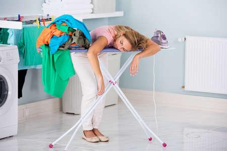 Mujer joven cansado que duerme en tabla de planchar junto a la pila de ropa en casa