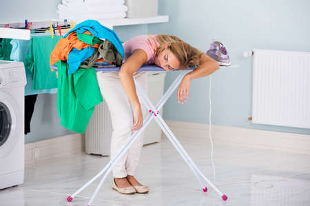 chores: Young Tired Woman Sleeping On Ironing Board Next To Pile Of Clothes At Home Stock Photo