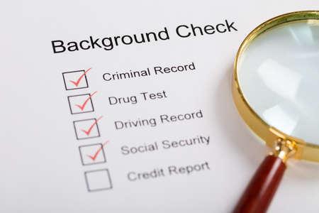 Vista de alto ângulo da lupa sobre o formulário de verificação de antecedentes