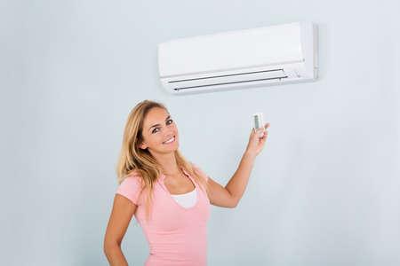 自宅のエアコンの前でリモコンを持って幸せな女の肖像