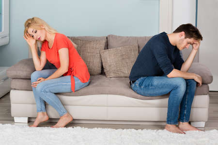 divorcing: Sad Angry Divorcing Couple Sitting Back To Back On Sofa At Home