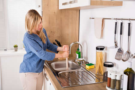 stoppage: Young Woman Using Plunger In Blocked Kitchen Sink To Unclog Drain At Home Stock Photo