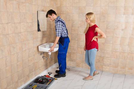 maintenance fitter: Young Handyman Installing Sink With Young Woman Standing In Bathroom