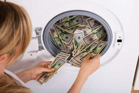 Close-up Of Person Hand Inserting Dirty Money In Washing Machine Stock Photo