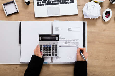 hand writing: High Angle View Of A Accountant Calculating Invoice Using Calculator On Wooden Desk