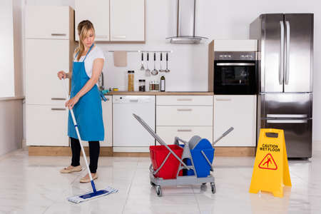 Cleaning Service Maid Using Mop To Clean Kitchen Floor At Home