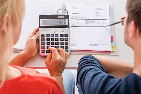 calculation: High Angle View Of Couple Calculating Invoice, Taxes And Family Budget At Home