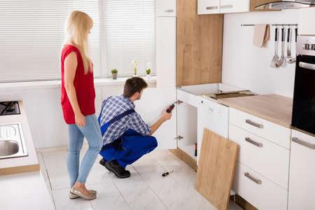 Fijación reparador o la instalación de la puerta del mueble de la cocina del fregadero delante de la mujer Foto de archivo