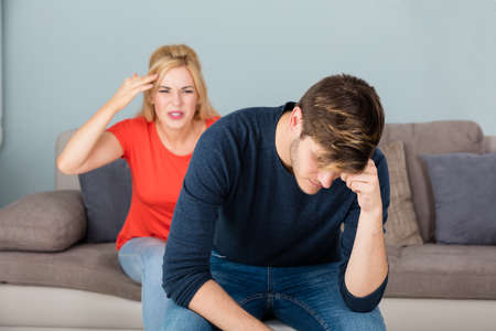 unhappy man: Unhappy Young Woman Sitting On Couch Having Arguing And Quarreling With Man At Home