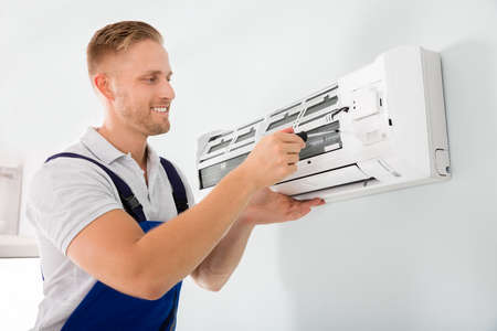 Happy Male Technician Repairing Air Conditioner With Screwdriver Stock Photo