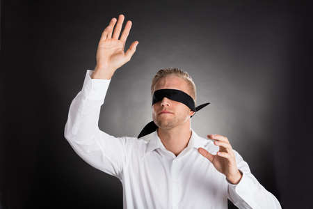 Young Blindfolded Confused Businessman Against Grey Background