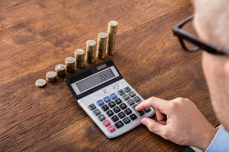 calculation: Person Hand Doing Calculation On Stacked Coin And Piggybank At Wooden Desk. Income Tax Concept