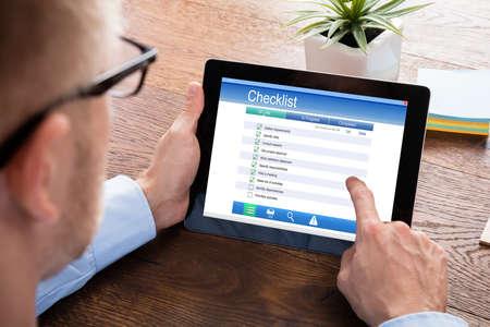 Close-up Of A Businessperson Filling Checklist Form On Digital Tablet At Wooden Desk