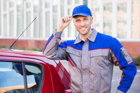 uniformes: Retrato de un hombre joven feliz que se coloca cerca del coche