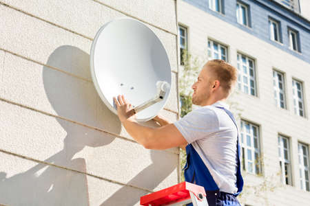 cable tv: Young Man Fitting TV Satellite Dish To Wall Stock Photo
