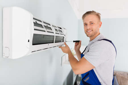 Young Male Technician Fixing Air Conditioner With Screwdriver Stock Photo