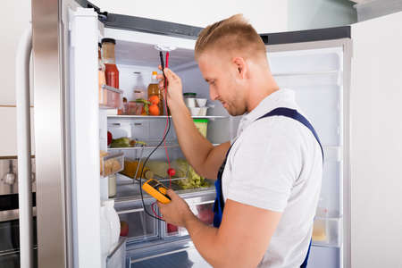 Young Repairman Checking Refrigerator With Digital Multimeter 版權商用圖片