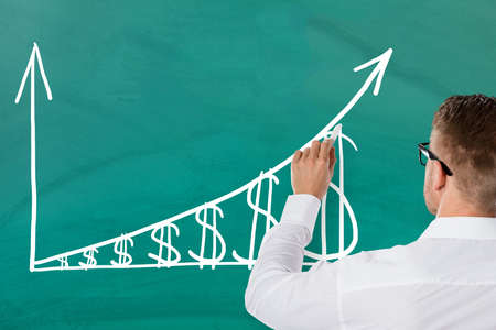 Businessman Showing Inflation Concept With Increasing Dollar Graph On Green Blackboard. Salary Growth Concept Stock Photo