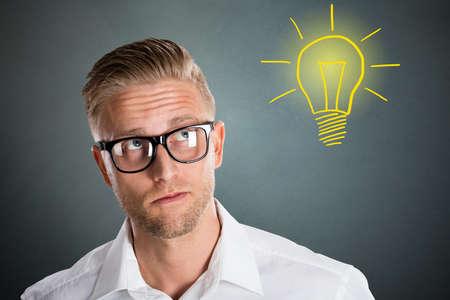 Inteligente hombre joven con la expresión pensativa con la idea de la bombilla sobre fondo gris