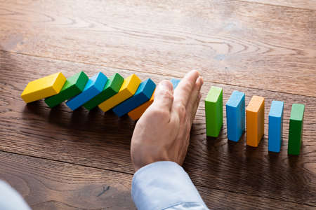 fear: Person Hand Stopping Falling Dominoes From Continuous Toppled On Wooden Desk. Business Risk Concept