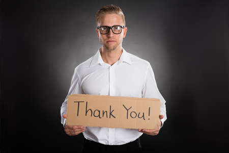 written: Man Holding Cardboard With Thank You Text Written On It Against Black Background