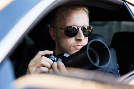 Private Detective Sitting Inside Car Photographing With SLR Camera Imagens - 70823994