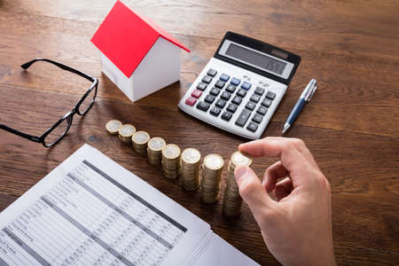 High Angle View Einer Person Stapeln Münzen In Der Nähe Haus Auf Hölzernen Schreibtisch. Eigentumssteuererklärung