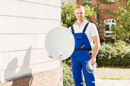 technician: Portrait Of A Happy Male Technician With TV Satellite Dish