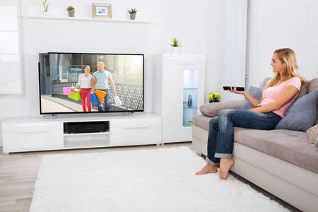 women sitting: Young Happy Woman Sitting On Couch Watching Romantic Movie On Television At Home