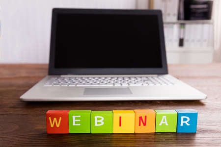 Webinar Text On Blocks In Front Of Laptop Over Wooden Desk Stock Photo