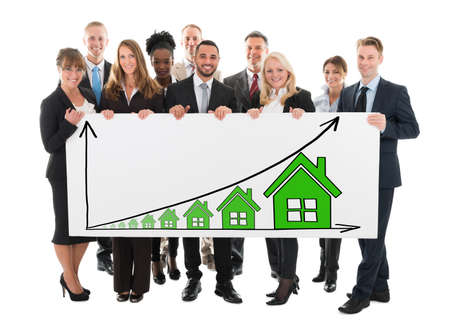 Diverse Business People Holding Billboard Showing House Rising Concept On White Background photo