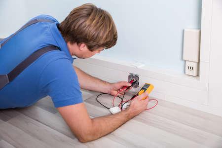 Elektricien controleren Socket Voltage Met behulp van multimeter in een muur armatuur