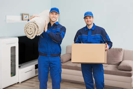 Portrait Of A Two Male Movers Carrying Rolled Carpet And Cardboard Box In House Banque d'images