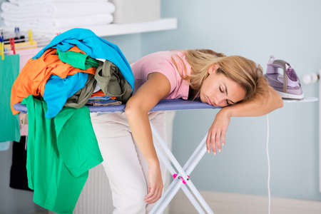 Young Fatigue Woman Sleeping On Ironing Board Next To Piles Of Clothes At Home