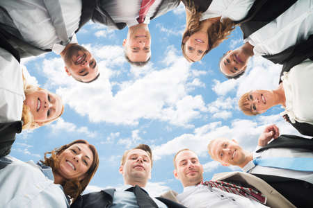 Portrait Of A Multiethnic Businesspeople Forming Huddle Against Sky photo