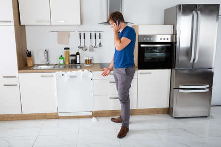 Young Man Shocked On Seeing Foam Coming Out Of Dishwasher At Home Stock Photo