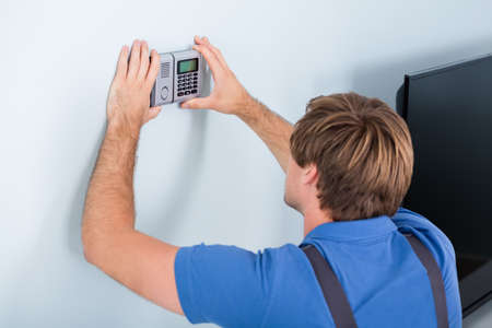 pin code: Rear View Of Repairman Installing Security System Against Wall Stock Photo