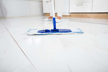 regular people: Cleaning Service Woman Mopping The Floor In Kitchen Inside House